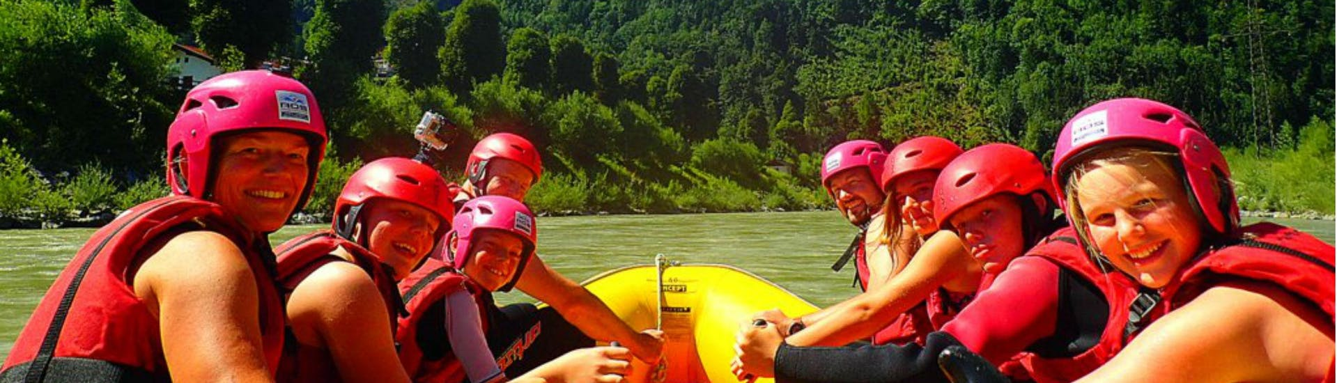 A group of people having fun rafting down Salzach River on their tour with Torrent Outdoor Experience.