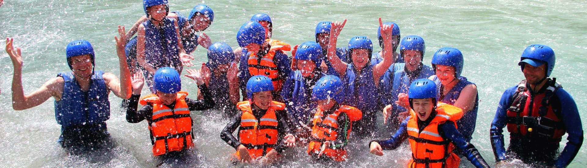 "A group of kids splashing in the Isel river on their Rafting ""Kids"" Tour together with an experienced rafting guide from Eddy Rafting."