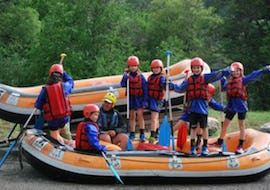 Kids are standing on a raft ready to start their Rafting on the Guisane River for Kids (8-12 years) with Rivieres Evasion.