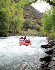 Two groups of people are paddling downstream while rafting in Llavorsí.