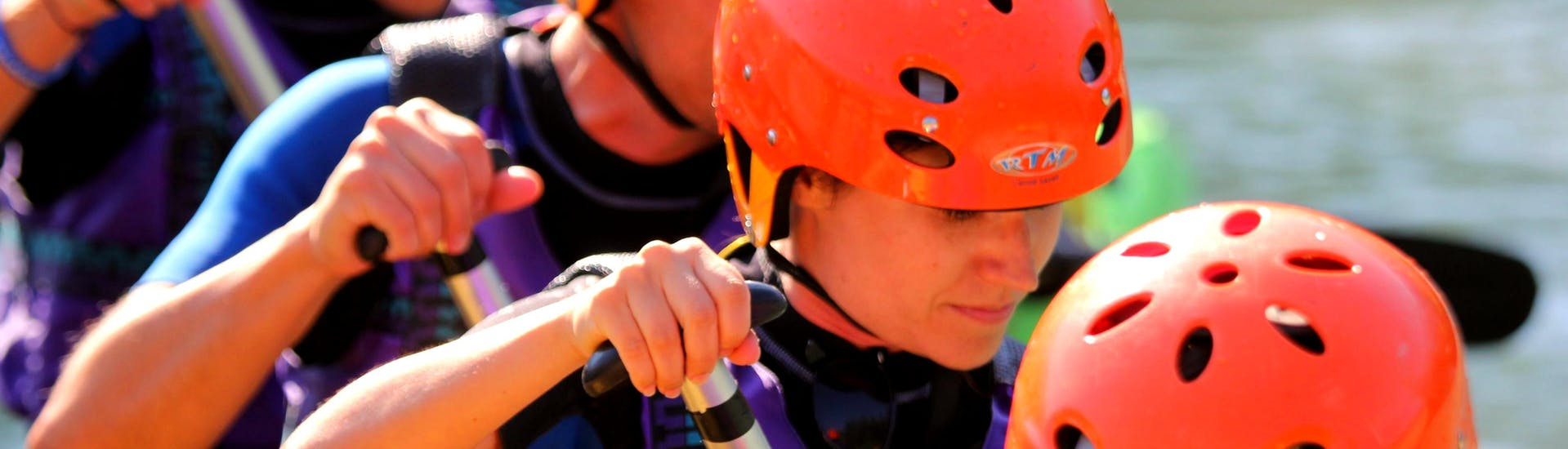 A group of people wearing orange helmets row during Rafting on the Adda - Full Fun of Rafting Lombardia.