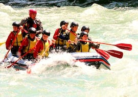 A raft with a team of 8 people is going down the Adda during the Rafting on the Adda - Full Fun of Rafting Lombardia.