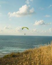 Una foto de un vuelo sobre una playa en el hermoso lugar de Sopelana mientras se vuela en parapente.
