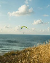 A photo from a man above a beach in the beautiful place of sopelana while paragliding.