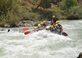 The tour participants paddle together with a guide from OcioAventura Cerro Gordo through the Rio Genil during the rafting whitewater trail.