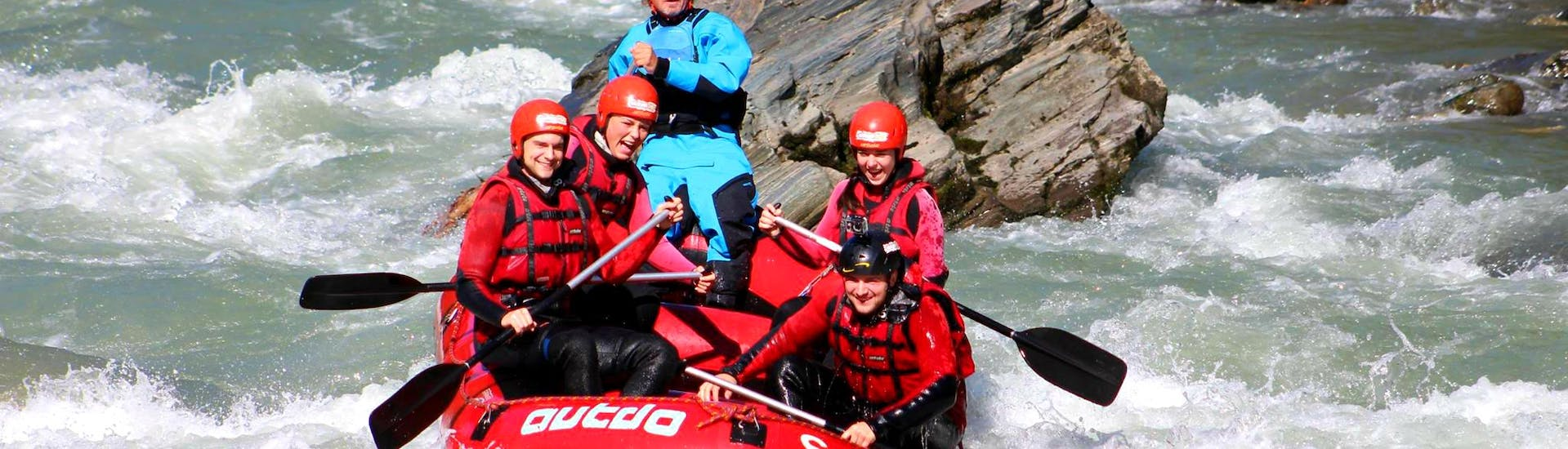 """A rafting group conquering the waves and rapids of Salzach river on their Rafting Tour """"Wild Water"""" together with an experienced guide from Outdo Zell am See Rating & Canyoning."""