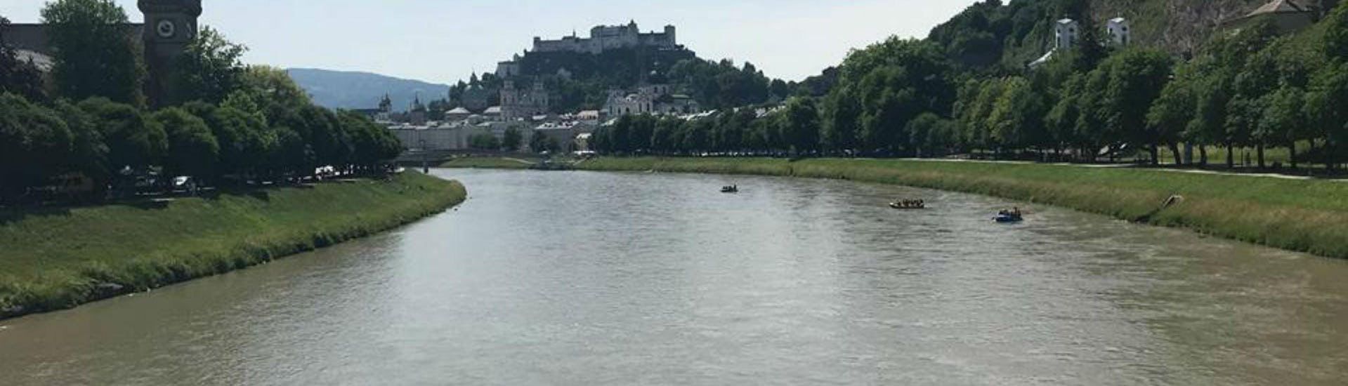 A group of people enjoying the magnificent view on the City of Salzburg during their Rafting tour on Salzach river with Torrent Outdoor Experience.