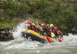 Eine Gruppe von Leuten, die bei ihrer Rafting Tour mit Torrent Outdoor Experience auf den Wellen der Salzach reitet.