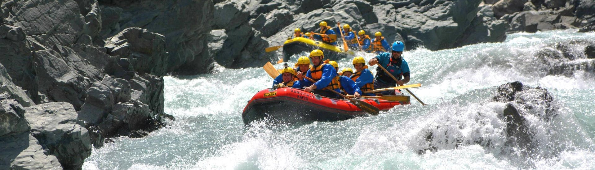 A group of rafters is paddling down a narrow section of the river during their Grade 5 Rafting Adventure in Rangitata Gorge organized by Rangitata Rafts.