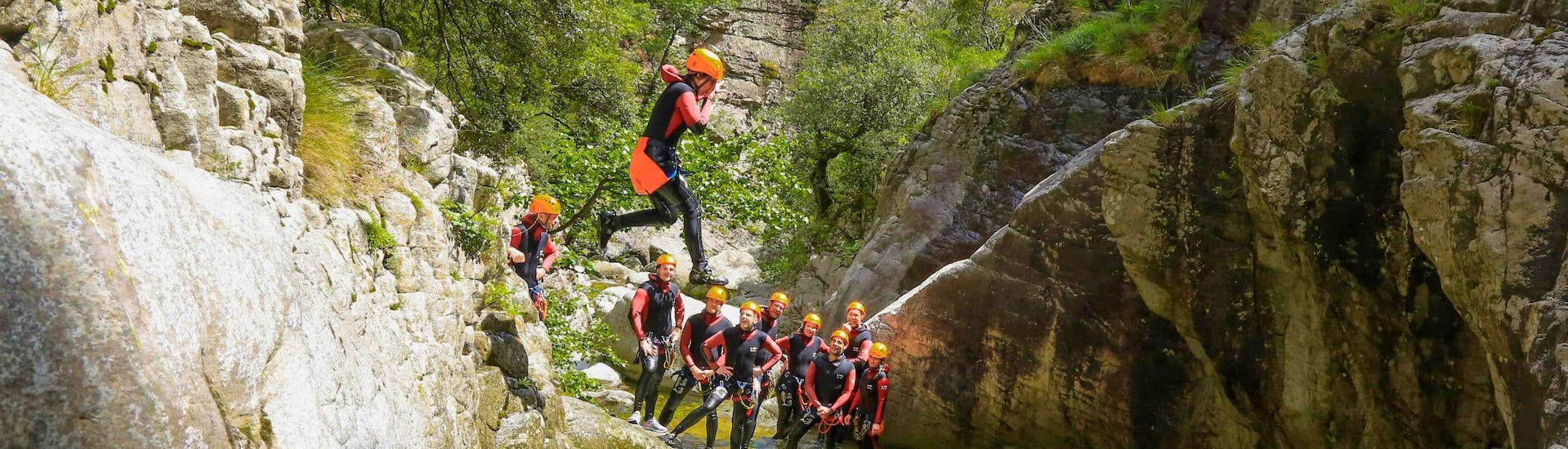 A tourist is jumping in the Richiusa canyon during his activity canyoning with reves de cimes.