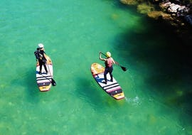 Two participants of the River SUP Tour on the Loisach with Bavariaraft are paddling along the river on their SUP boards.