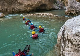 Participants of the river trekking tour Couloir Samson with Yeti Rafting are floating in the emerald waters of the Gorges du Verdon.