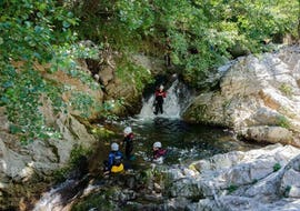 Canyoning enthusiasts are having fun in a natural pool while doing their River Trekking for Families - Canyon de l'Azero with Les Intraterrestres.