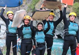 A family is smiling at the camera before jumping into the waters of the Kawarau River to enjoy the activity Riversurfing on the Kawarau River for Families organized by Serious Fun Riverboarding.