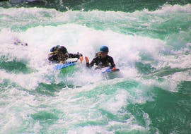 A experienced guide from Serious Fun Riverboarding is taking a participants of the activity Riversurfing on the Kawarau River near Queenstown to discover the best spots on the river to have fun with the rapids and the whirlpools.