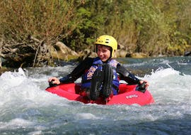 A boy is floating along the river during the Rivertubing on Cetina River organized by Adventure Dalmatia.