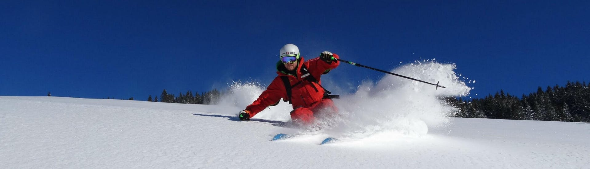 A ski instructor from the ski school S4 Snowsport Fieberbrunn is skiing through deep powder snow in the tyrolean ski resort of Fieberbrunn.
