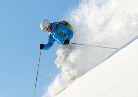 """Ein Skifahrer fährt im Rahmen des Angebots """"Privater Freeride Kurs - Alle Levels"""" der Skischule Widmann Mountain Sports im Tiefschnee in Richtung Tal während der Schnee aufgewirbelt wird."""