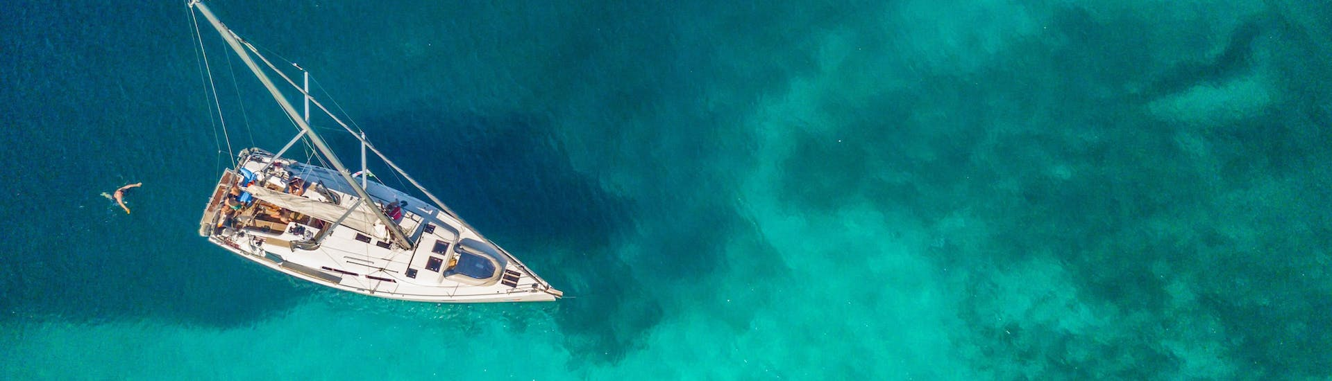 Sailboat from above in emerald water