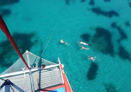 Tour participants bathe in crystal clear water during the Sailing Catamaran Tour with Snorkeling, Paella & Drinks organized by Robinson Boat Trips.