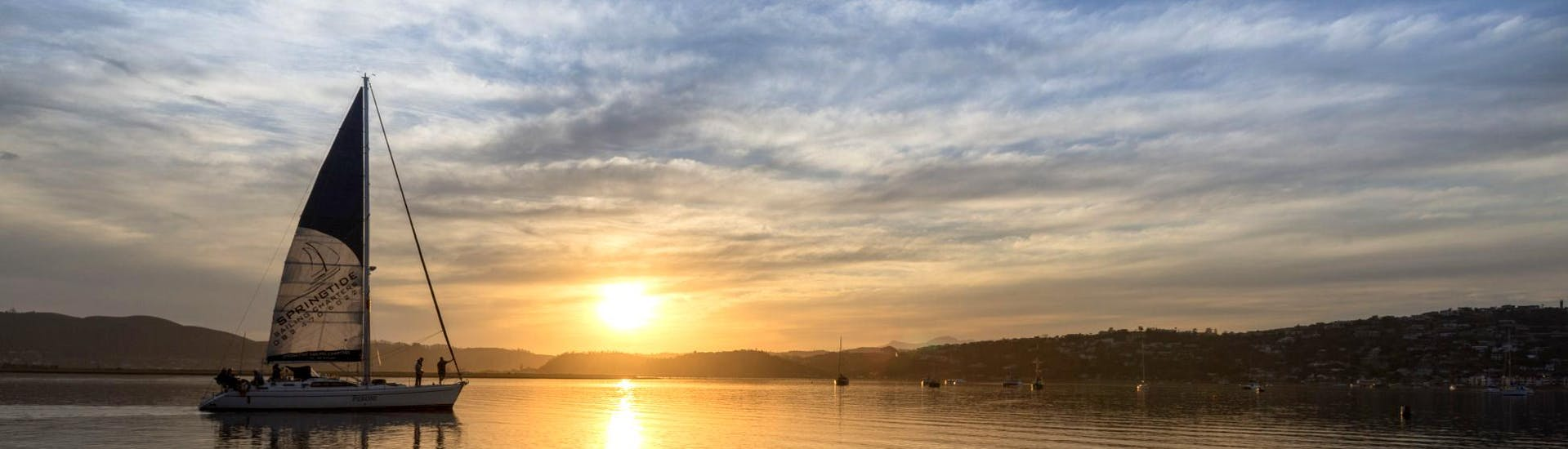 During the Sunset Sailing Tour from Knysna with Finger Dinner organised by Spring Tide Charters Garden Route, tourists are enjoying amazing views of the Knysna's scenery at sunset.