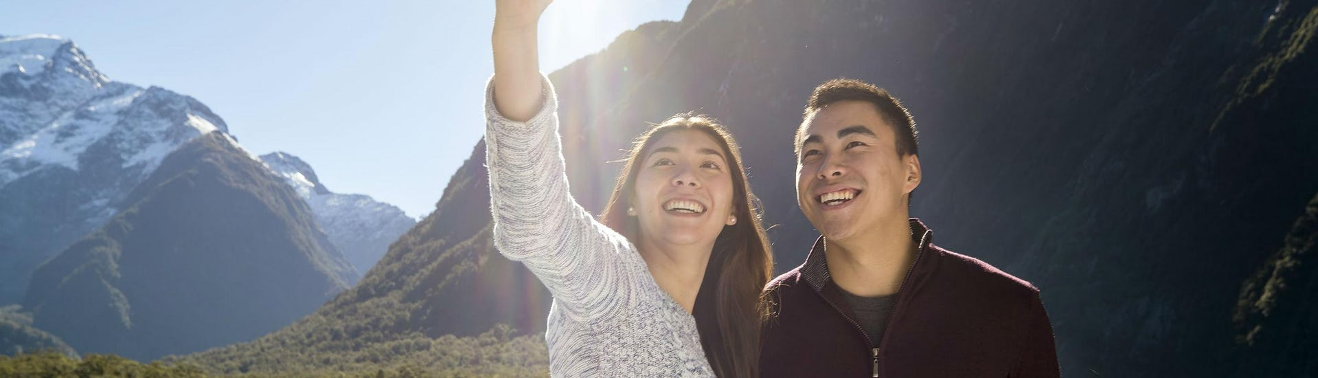 A couple is smiling at the camera as they take a selfie during the Scenic Cruise in Milford Sound - Winter with Southern Discoveries.