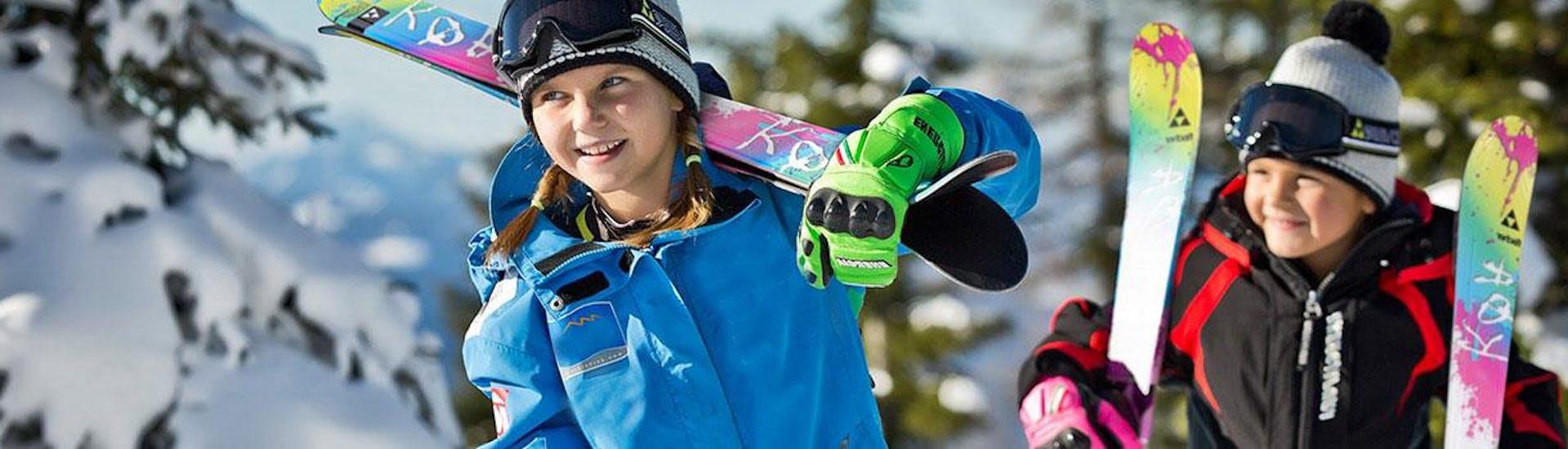 Ein junges Mädchen und ein junger Bub tragen ihre Ski um mit ihrem Skikurs mit der Schneesportschule Black Forest Magic im Skigebiet Feldberg beginnen zu können.