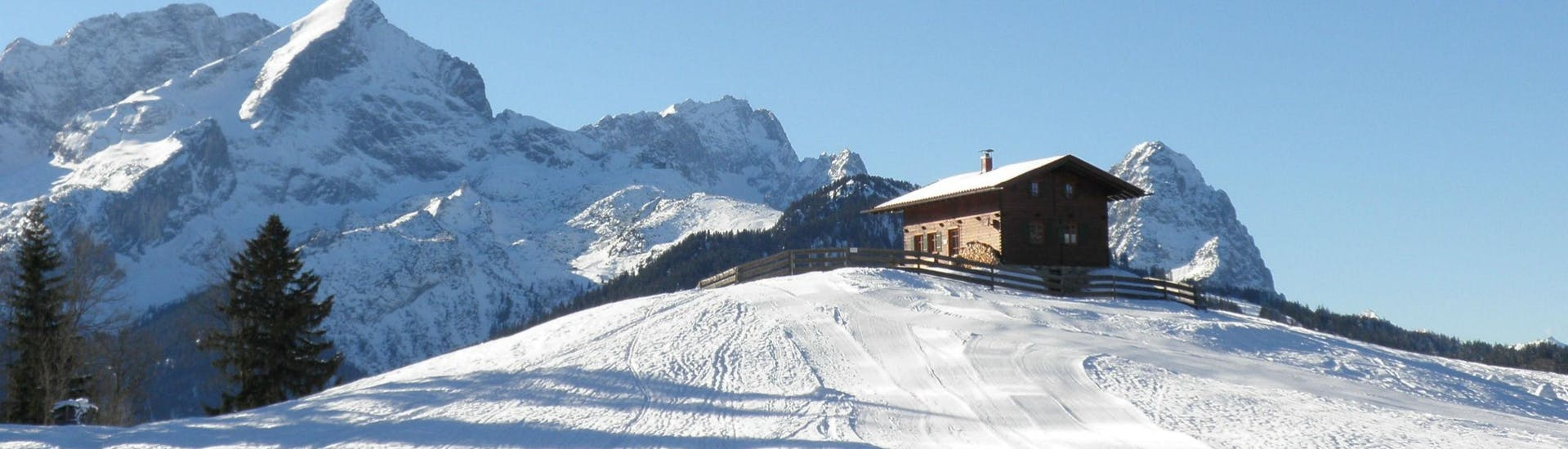 A small hut is perched on top of a ski slope in the Ski Resort of Garmisch-Classic, where the ski school Schneesportschule Morgenstern carries out its ski lessons.