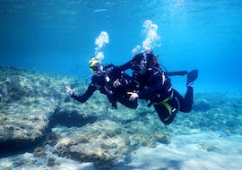 A woman enjoying her first diving experience in her Discover Scuba Diving Tour in Mykonos together with an experienced instructor from Mykonos Diving Center.
