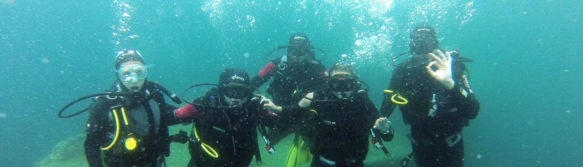 A group of friends are posing underwater during their PE12 & SSI/PADI Scuba Diver Course for Beginner with Le Kalliste Plongée.