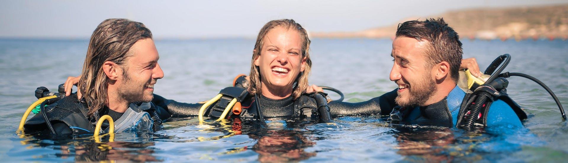 Drie duikers zijn samen in het water afgebeeld en lijken te genieten van hun duikcursus.