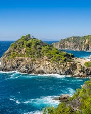 The beautiful Porquerolles Island and windy sea are pictured which is an ideal place for scuba diving in Hyères.