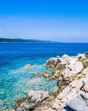 An image of the clear blue waters along the coastline of Sardinia that are frequently explored by visitors who go scuba diving near Porto Pollo.