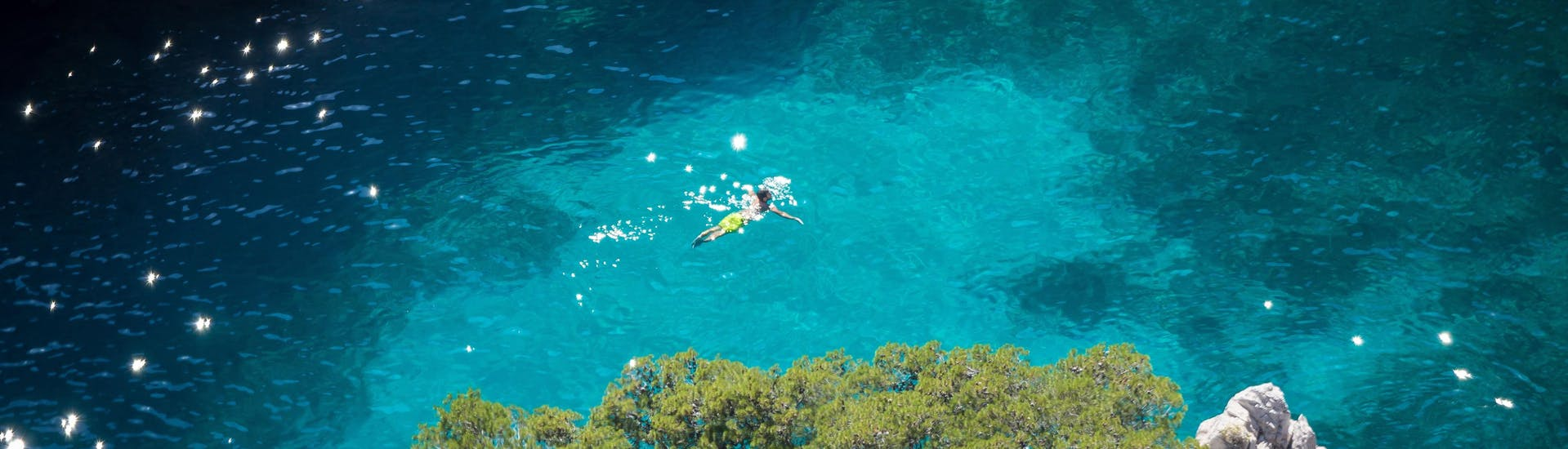 A swimmer is swimming in the turquoise waters of the Calanques National Park, one of the top diving and snorkeling spots on the French Riviera.