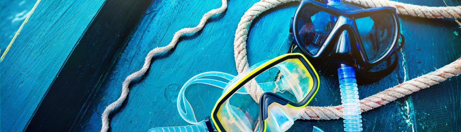 Two sets of goggles and a snorkel lie prepared on a boat, ready to be taken scuba diving in Mallorca.