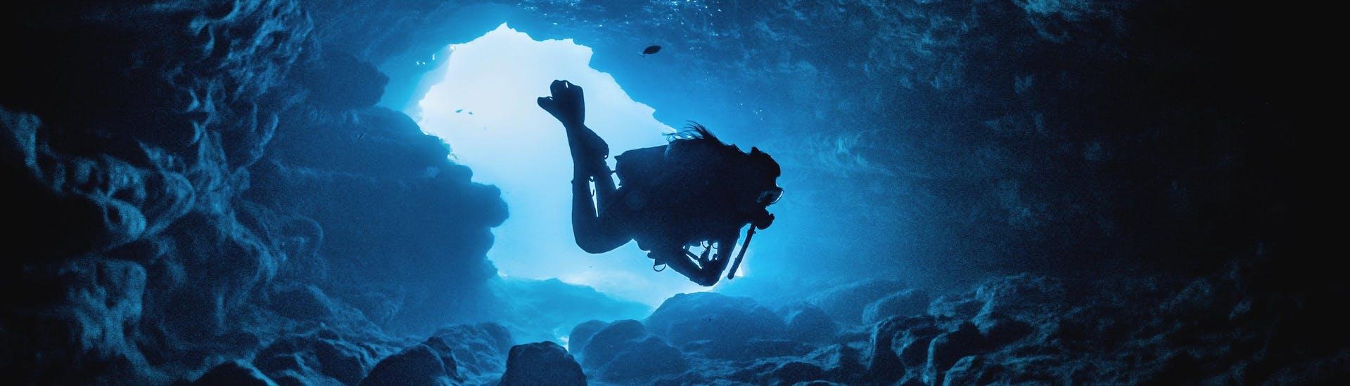 Ein Gerätetaucher erkundet eine der vielen Unterwasserhöhlen Maltas, einem beliebten Reiseziel in Europa für Taucher.