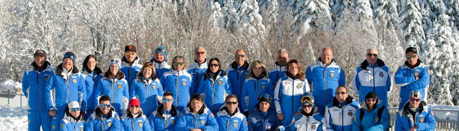 The ski instructors from the ski school Scuola di Sci Abetone are gathered in the snow with smiling faces that invite everyone to join their ski lessons.