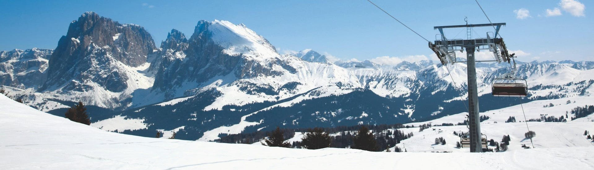 View over the sunny mountain landscape while learning to ski with the ski schools in Alpe di Siusi.