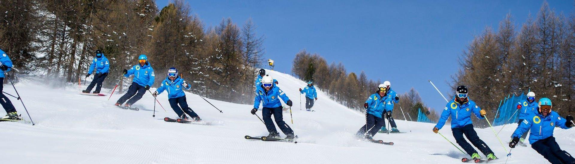 A group of ski instructors from the ski school Scuola di Sci Azzurra Livigno are collectively skiing down a ski slope in Livigno, all wearing their uniform.