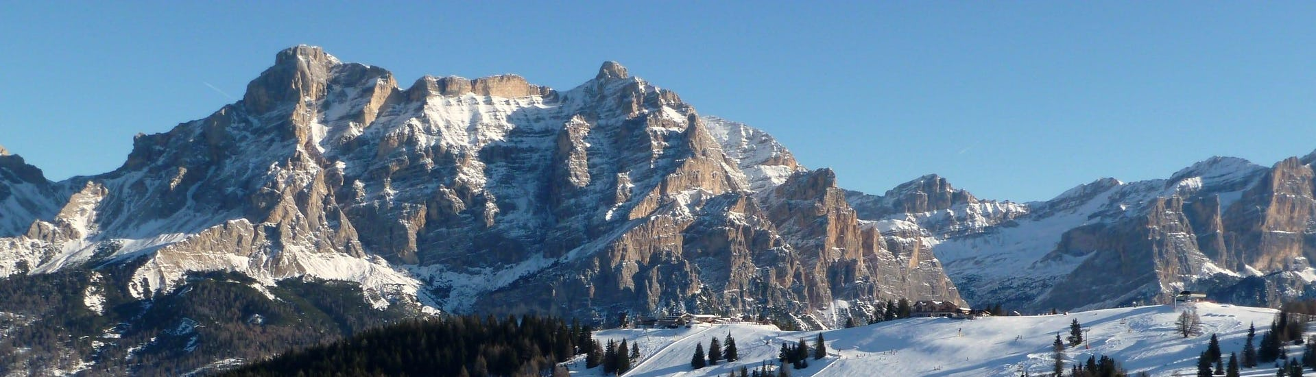 View over the sunny mountain landscape while learning to ski with the ski schools in Corvara.