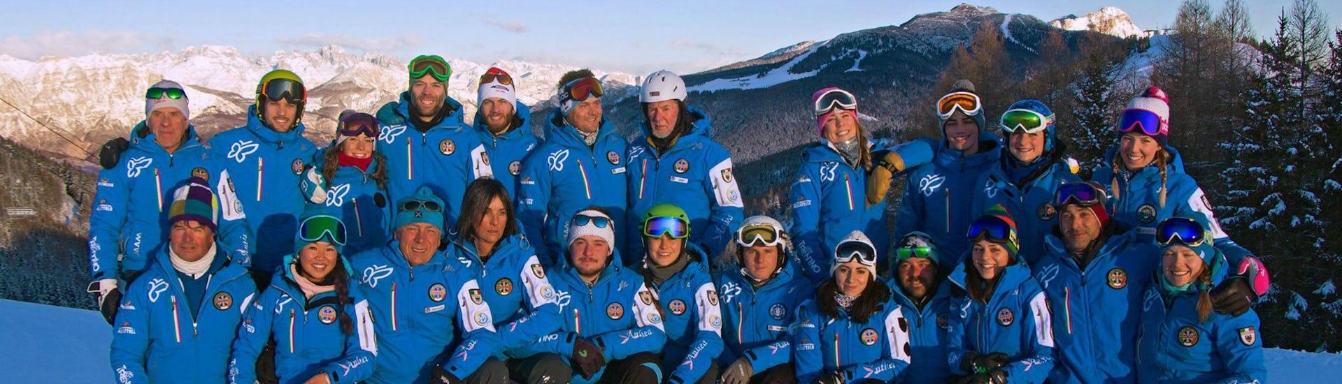Die Skilehrer der Skischule Scuola di Sci e Snowboard Alpe Cimbra posieren gemeinsam auf einer der Pisten auf der sie Ihre Skikurse im Skigebiet Folgaria durchführen.