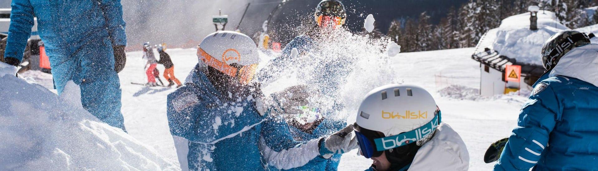 The ski instructors from the ski school Scuola di Sci e Snowboard Cristallo Cortina are playing around in the snow in the ski resort of Cortina d'Ampezzo, where they offer their ski lessons.
