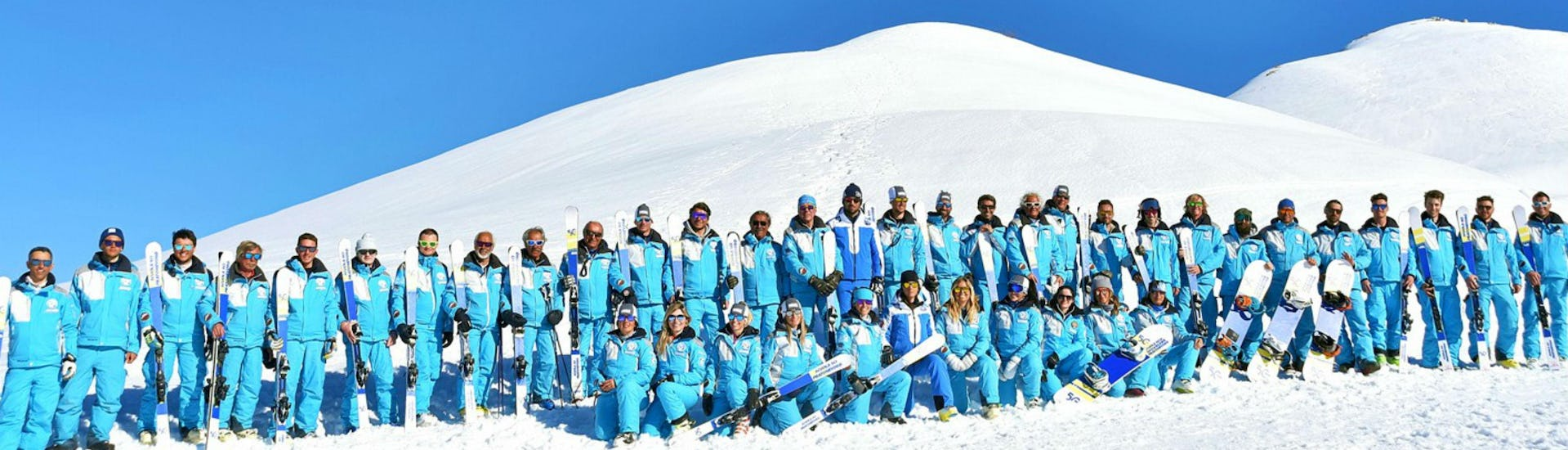 The ski instructors from the ski school Scuola di Sci e Snowboard Prato Nevoso are posing for a group photo.