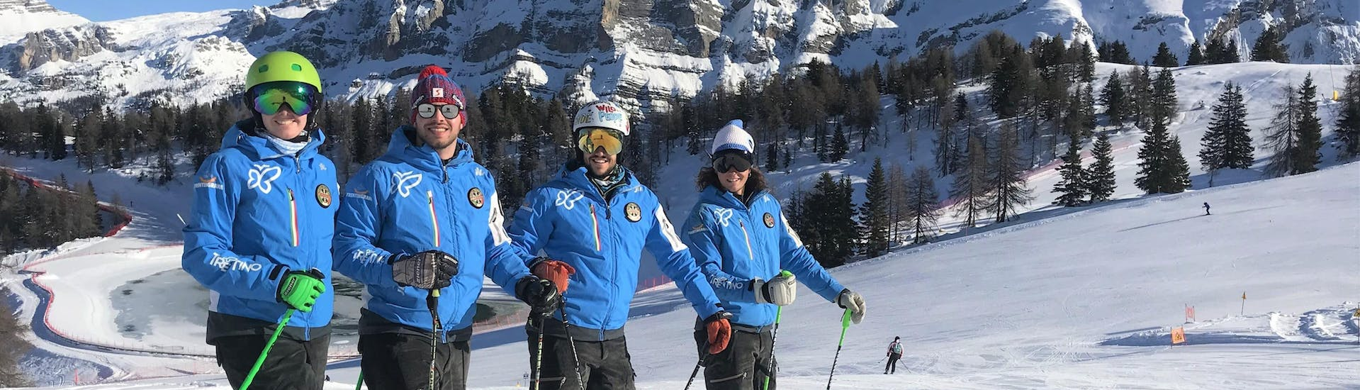 Some instructors of the ski school Scuola di Sci Pinzolo are smiling at the camera before heading to the slopes and give private and group lessons in the Val Rendena ski resort.