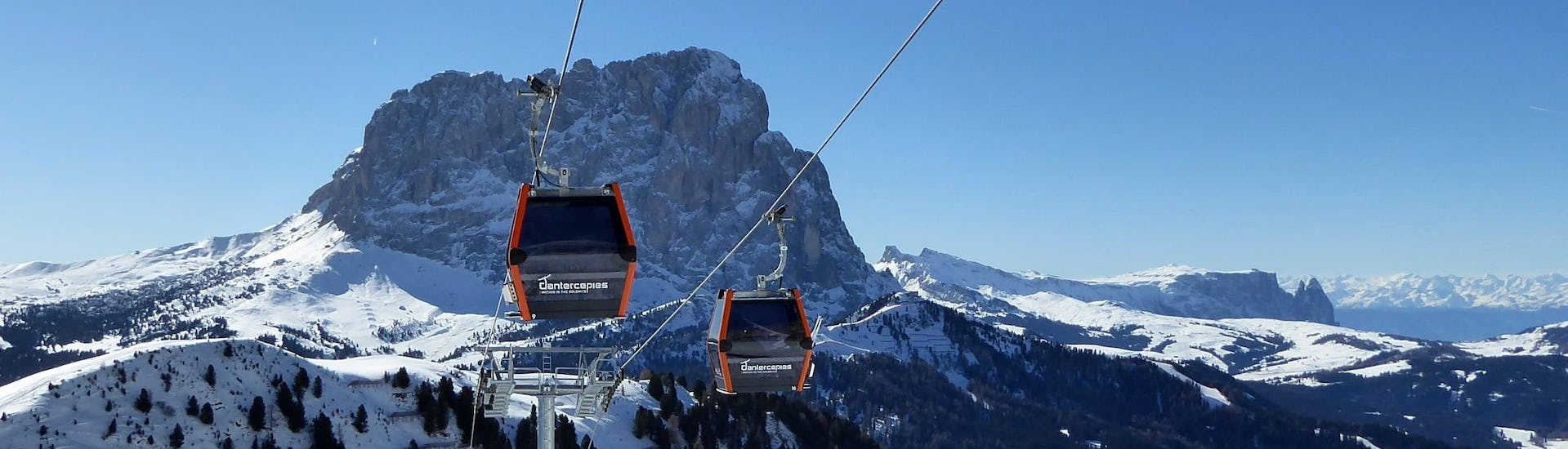 View over the sunny mountain landscape while learning to ski with the ski schools in Selva di Val Gardena.
