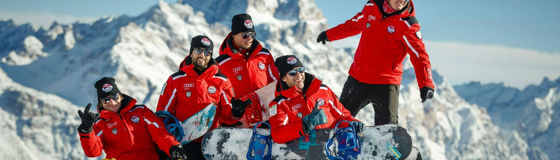 Eine Gruppe Skilehrer der Skisschule Scuola Sci Cortina posiert mit ihren Snowboards auf einem Schneehaufen im Skigebiet Cortina d'Ampezzo, wo sie eine breite Palette an Skikursen anbieten.