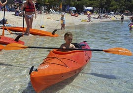 A child is trying to paddle a kayak during the Sea Kayak Rental - Makarska Riviera offered by Butterfly Diving & Sailing.