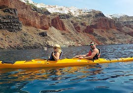 During a sea kayak tour, a couple is paddling with a professional kayak guide from Santorini Sea Kayak around the magical city of Santorini.