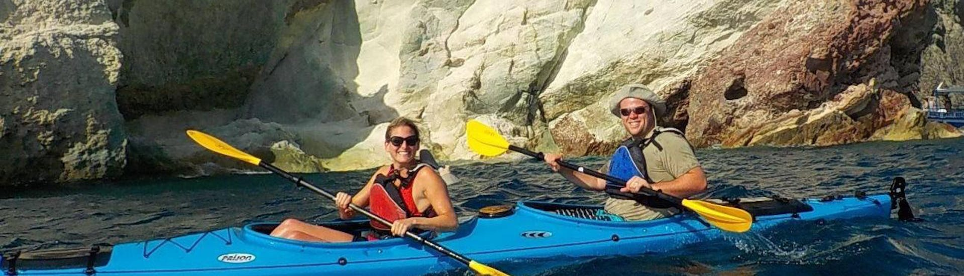 Led by a local certified kayak guide from Santorini Sea Kayak, a couple is paddling along a rocky coast of Santorini during a sea kayak tour.