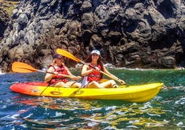 Two girls are paddling close to the coastal area of São Miguel during the Sea Kayaking along the Coast in Caloura with Fun Activities Azores Adventures.